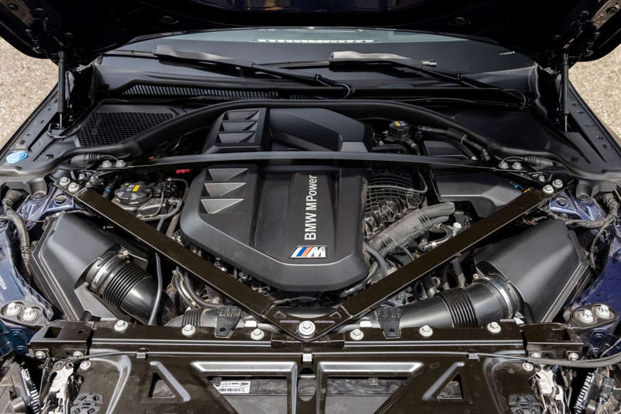 a motorcycle parked next to a car engine: 2021 BMW M3 Competition