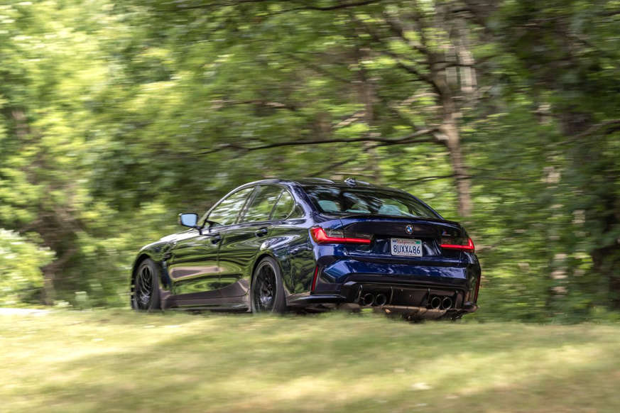 a car driving down a dirt road: 2021 BMW M3 Competition
