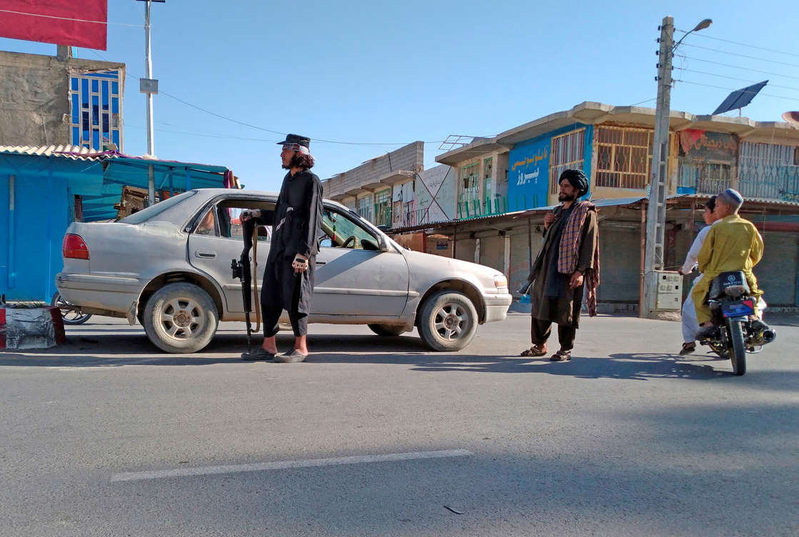 Taliban fighters stand guard at a checkpoint inside the city of Farah, capital of Farah province southwest of Kabul, Afghanistan, Wednesday, Aug. 11, 2021. (AP Photo/Mohammad Asif Khan)