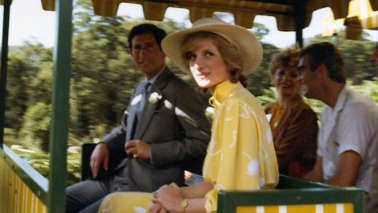 a group of people sitting at a table: The Prince and Princess of Wales, Charles and Diana, ride the Big Pineapple train during their visit to the Sunshine Coast in 1983. (Supplied: Queensland State Archives)