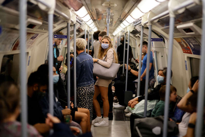 People, many wearing face coverings to combat the spread of the coronavirus, travel on the Jubilee line of the London Underground on August 9, 2021. - After updated guidance from British health regulators, coronavirus vaccinations have been extended to those aged 16 and 17 without underlying health issues, but not to younger healthy teenagers as in many other Western countries. (Photo by Tolga Akmen / AFP) (Photo by TOLGA AKMEN/AFP via Getty Images)