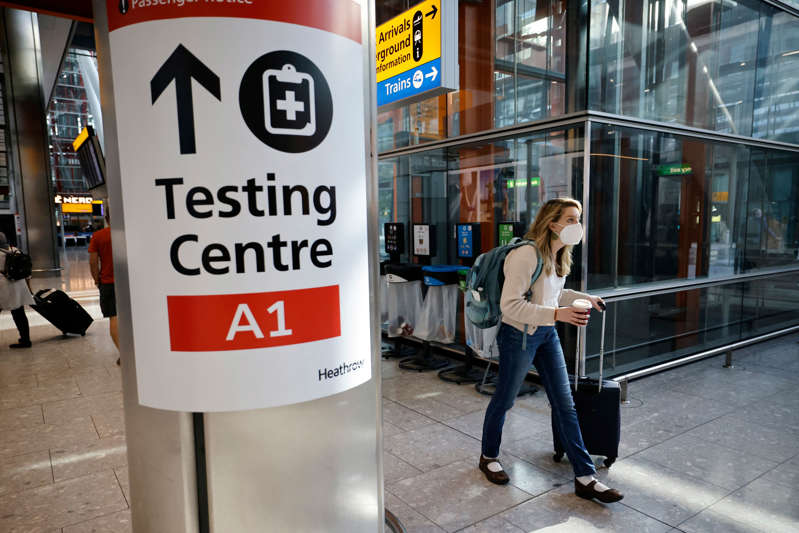 A traveller walks past a sign directing the public to a Covid testing centre at Terminal 5 in west London on August 2, 2021 as quarantine restrictions ease. - People fully vaccinated in the United States and European Union, except France will now be allowed to travel to England without having to quarantine on arrival. (Photo by Tolga Akmen / AFP) (Photo by TOLGA AKMEN/AFP via Getty Images)