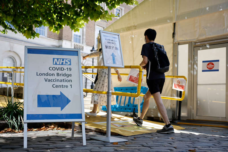 People are directed at the entrance to the London Bridge Vaccination Centre as people arrive to receive doses of the coronavirus Covid-19 vaccine in London on August 9, 2021. - After updated guidance from British health regulators, coronavirus vaccinations have been extended to those aged 16 and 17 without underlying health issues, but not to younger healthy teenagers as in many other Western countries. (Photo by Tolga Akmen / AFP) (Photo by TOLGA AKMEN/AFP via Getty Images)