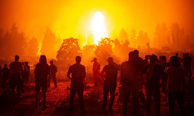 a group of people standing around a fire: Photograph: Angelos Tzortzinis/AFP/Getty Images