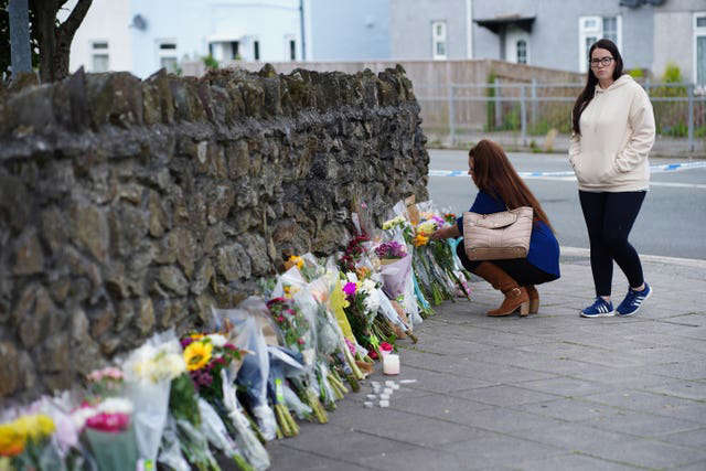 a person standing in front of a building: Floral tributes have been left by the scene in Keyham (Ben Birchall/PA)