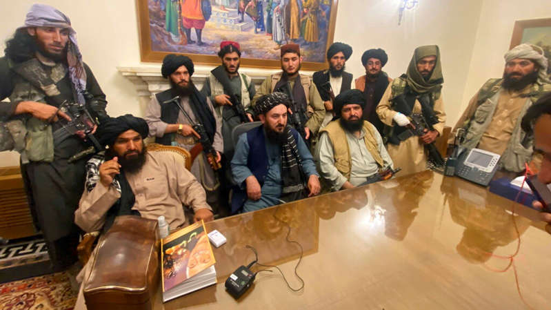 a group of people sitting at a table: Taliban fighters are pictured inside Kabul's presidential palace. Pic: AP