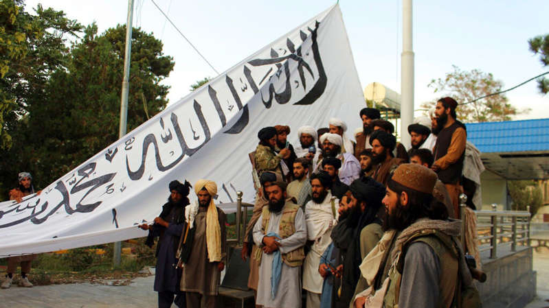 a group of people posing for the camera: Taliban fighters are pictured in Ghazni, southeastern Afghanistan as they raise their flag. Pic: AP