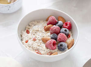 a bowl of fruit on a plate: oatmeal