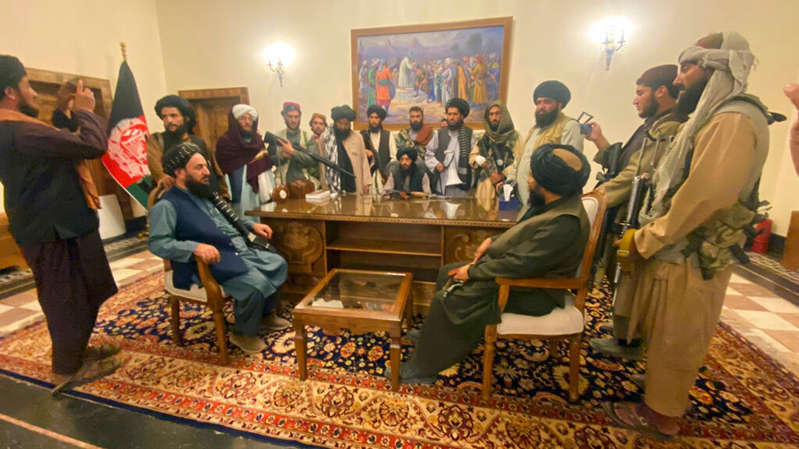a group of people standing in a room: A Taliban spokesman said the nature of its rule will 'become clear soon'. Pic: AP