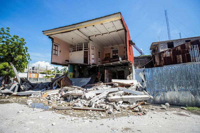 a pile of dirt in front of a building: A house destroyed following a 7.2 magnitude earthquake