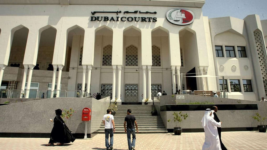a group of people walking in front of a building: The case, at Dubai Criminal Court, is being heard in the husband's absence.