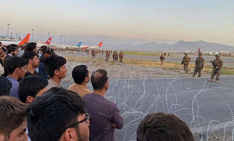 a group of people looking at a kite in front of a crowd: Afghans desperate to flee the country crowd the tarmac at Kabul airport, as US soldiers stand guard. Photograph: Shakib Rahmani/AFP/Getty Images