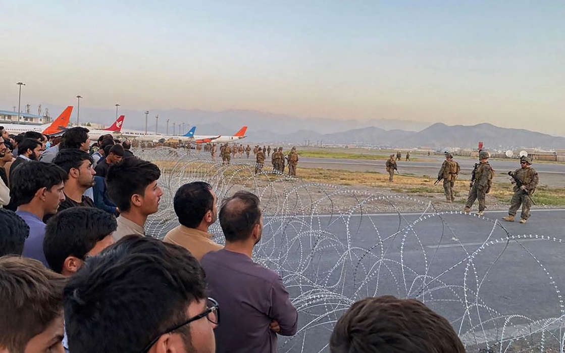 a group of people looking at a kite: Afghans crowd at Kabul airport as US soldiers stand guard