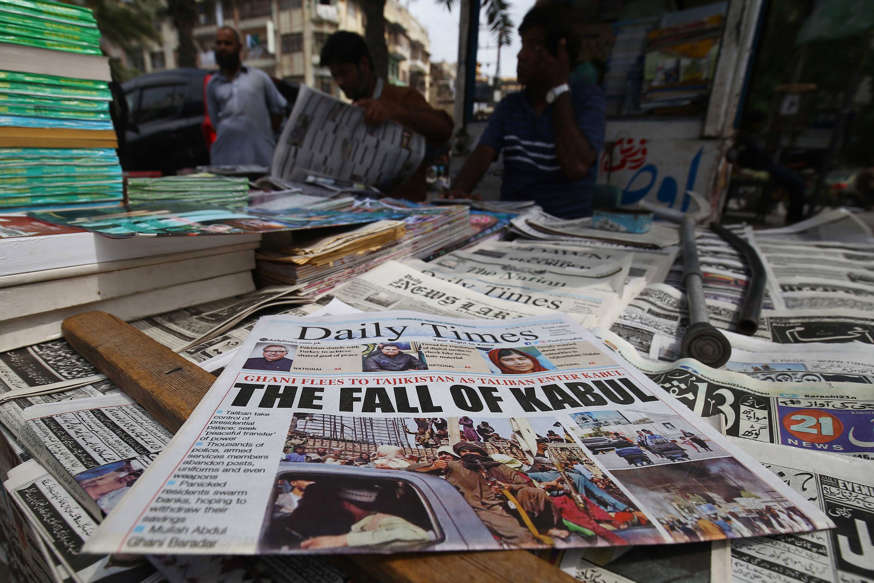 text: People read about the Taliban's takeover of Kabul at a newspaper stall in Karachi, Pakistan, on Aug. 16, 2021. (Shahzaib Akber/EPA-EFE/Shutterstock)