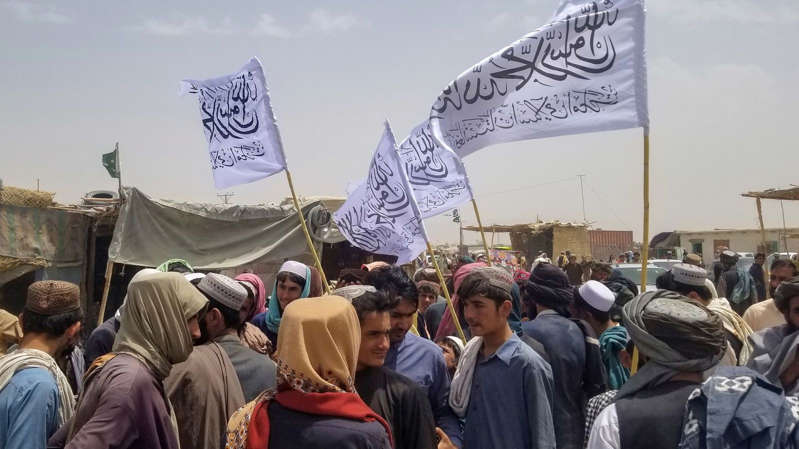 a group of people standing in front of a crowd: The Taliban have swiftly retaken control of Afghanistan