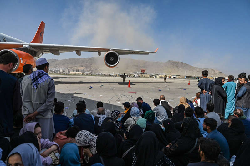a group of people standing around a plane: Afghan people sit as they wait to leave the Kabul airport in Kabul on August 16, 2021, after a stunningly swift end to Afghanistan's 20-year war, as thousands of people mobbed the city's airport trying to flee the group's feared hardline brand of Islamist rule.
