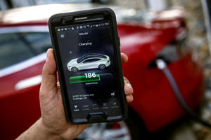 a close up of a hand holding a cellphone: A Tesla being charged in front of Harris Farms Restaurant in Coalinga, off Interstate 5. (Ricardo DeAratanha / Los Angeles Times)