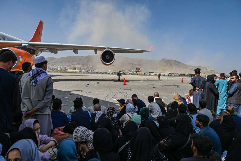 Afghan people sit as they wait to leave the Kabul airport in Kabul on August 16, 2021, after a stunningly swift end to Afghanistan's 20-year war, as thousands of people mobbed the city's airport trying to flee the group's feared hardline brand of Islamist rule.