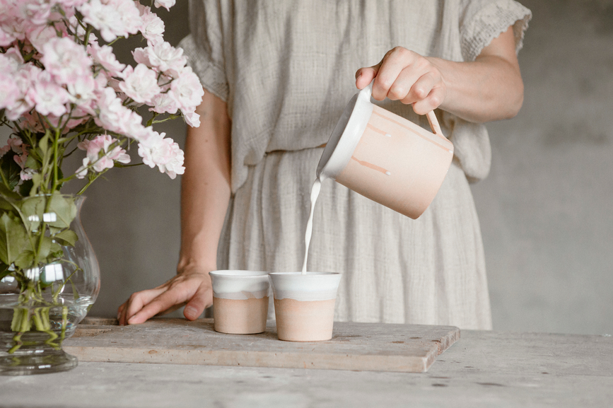 a person holding a cup: flax milk