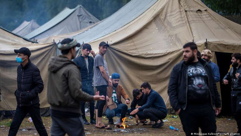 a group of people standing in a tent: Thousands of people are already in refugee reception centers in Lithuania