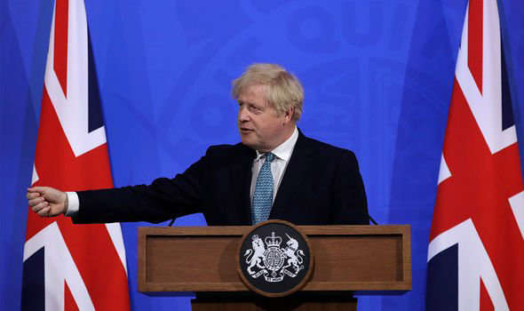 Boris Johnson holding a sign in front of a flag: Boris Johnson: The PM has recalled Parliament to discuss the unfolding crisis