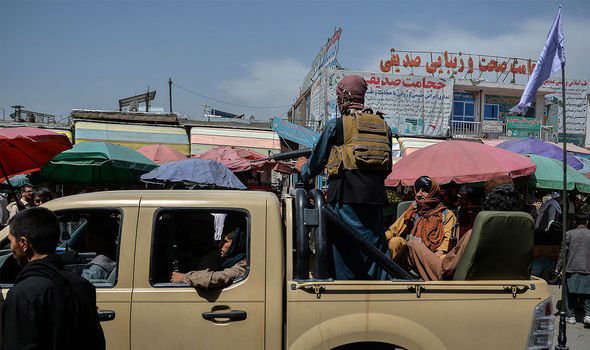 a group of people riding on the back of a truck: Afghanistan: The Taliban took Kabul over the weekend