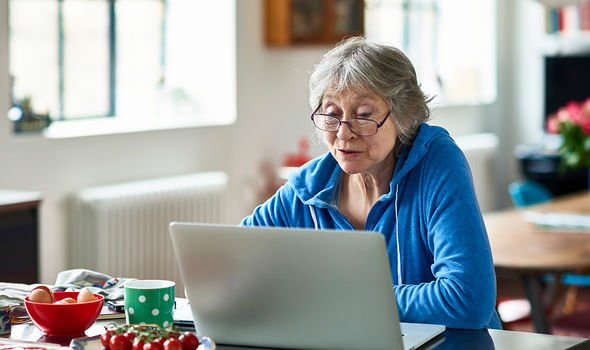 a woman sitting at a table using a laptop: Pension triple lock: Woman at computer