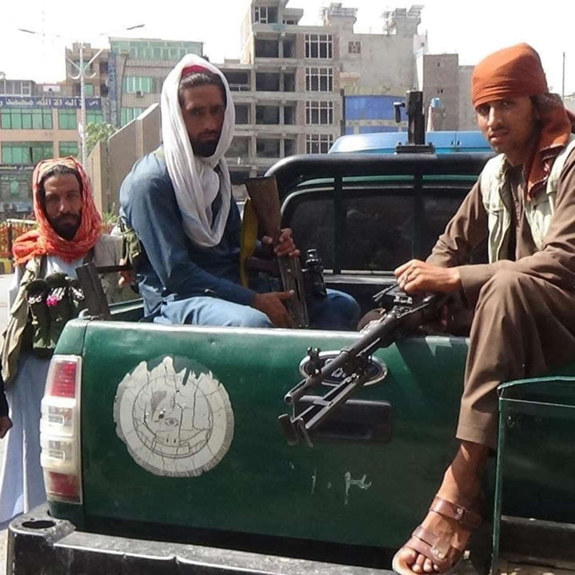 a man standing in front of a bus: Taliban patrols Jalalabad city