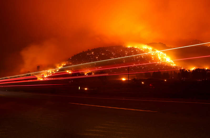 a bright light in front of a sunset: The Caldor Fire ravaged the forest community of Grizzly Flats, destroying most of the homes in the town as California's wildfires continue. The Dixie Fire burns in the hills on August 17, 2021 near Milford, California.