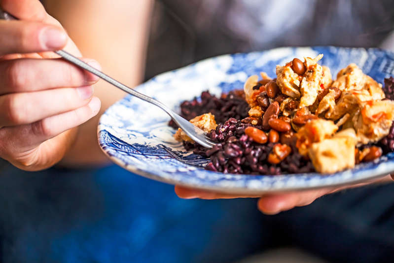 a hand holding a fork with a plate of food: Chicken curry with beans and rice is a great protein-rich meal. Getty