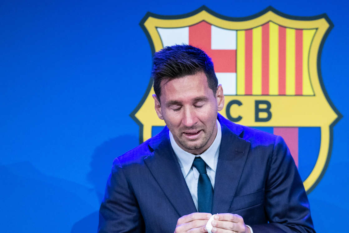 a man wearing a suit and tie: Lionel Messi