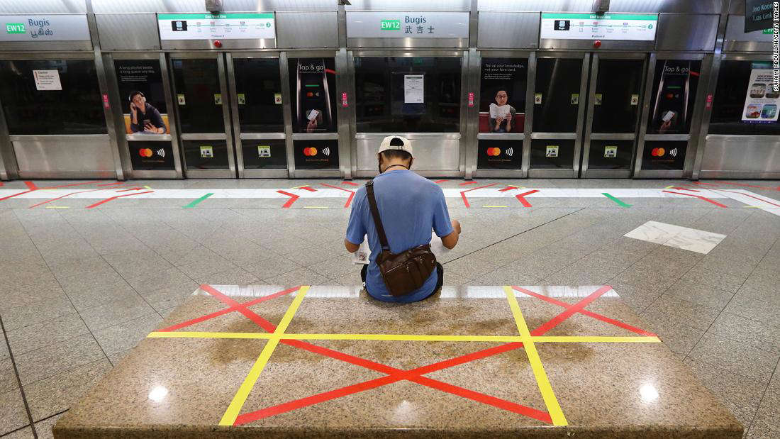 A man reading a newspaper sits on an unmarked safety distancing marker at a train station on April 21, 2020 in Singapore.