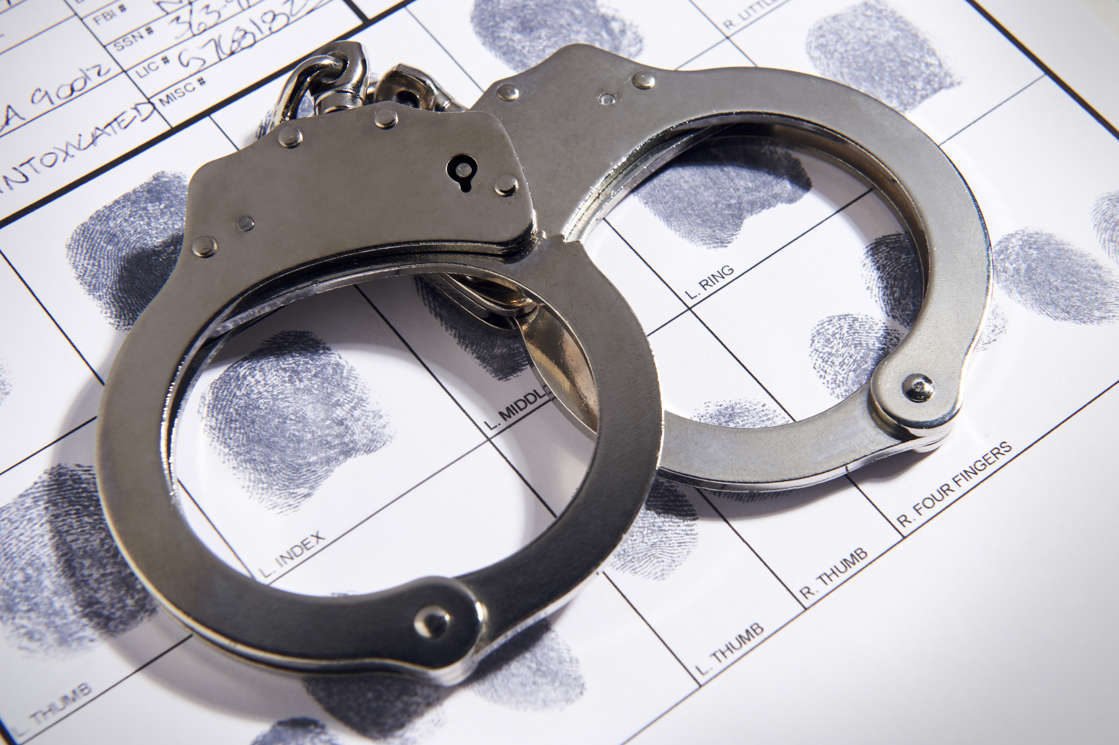 A stock photo of handcuffs and fingerprints. An Arizona man who spent over half his life behind bars is headed back to prison after robbing two bank tellers at gunpoint back in 2018.