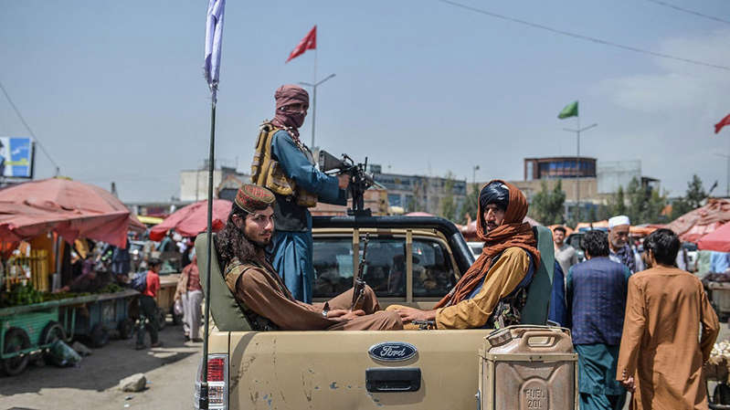 a group of people riding on the back of a truck: Heavy fighting reported in last Afghanistan province not under Taliban control