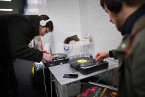 a man standing in a kitchen preparing food: Customers play albums on portable turntables at the Olympia record fair. There is an innate human desire to own a tangible object (Getty)