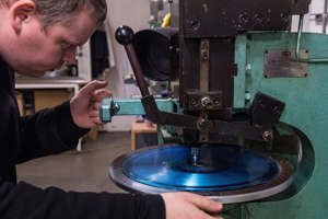 a man in a blue shirt: Vinyl Factory worker Martin Frings checks a finished master is usable. He looks at the grooves through a microscope (Getty)