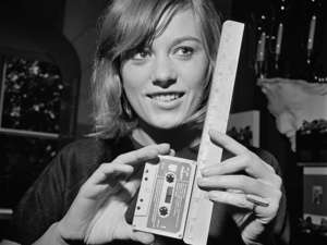 Madeline Kahn holding a cell phone: Elizabeth Jackson measures a new cassette tape of 'Jazz Sebastien Bach', an album by Les Swingle Singers, in August 1966 (Getty)