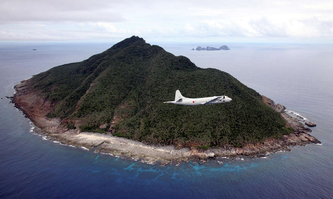 an island in the middle of a body of water: File photo: This photo taken on October 13, 2011, shows a P-3C patrol plane of the Japan Maritime Self-Defense Force flying over the disputed islets known as the Senkaku Islands in Japan and the Diaoyu islands in China, in the East China Sea.
