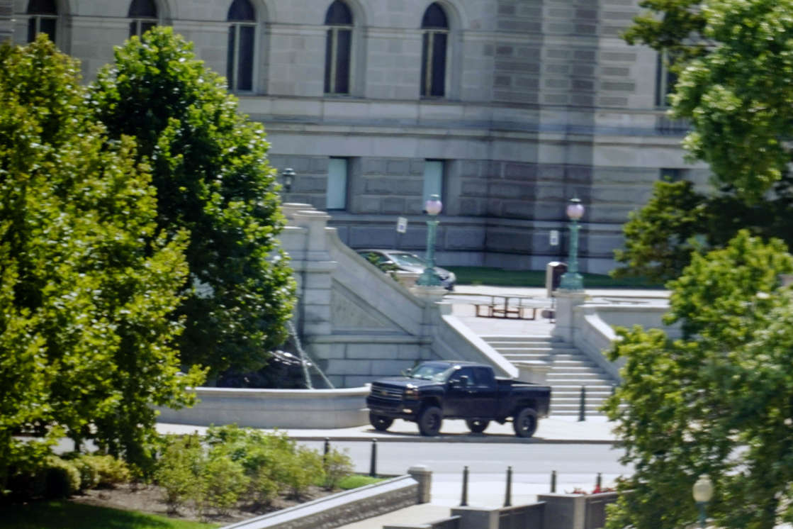 a car driving down a street next to a building: A pickup truck is parked on the sidewalk in front of the Library of Congress' Thomas Jefferson Building, as seen from a window of the U.S. Capitol, Thursday, Aug. 19, 2021, in Washington. / Credit: Alex Brandon / AP