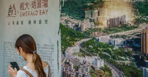 a woman talking on a cell phone: A banner promoting the Emerald Bay residential project outside the China Evergrande Centre in the Wan Chai area of Hong Kong, China, on Friday, July 23, 2021.