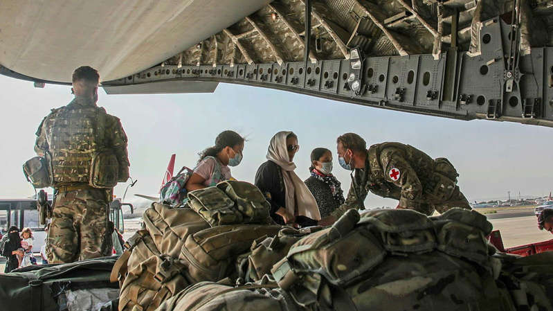a group of people standing next to a bag of luggage: British citizens and dual nationals residing in Afghanistan board a military plane for evacuation. Pic: Ben Shread/UK MOD