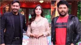 a person standing in front of Ajay Devgan, Nora Fatehi, Kapil Sharma posing for the camera: Ajay Devgn, Nora Fatehi and Kapil Sharma on the sets of the comedy show.