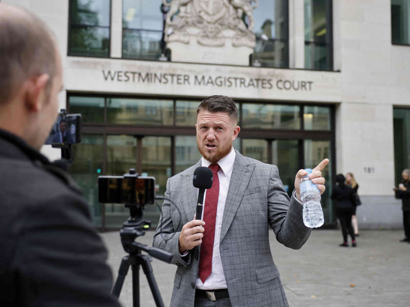 Tommy Robinson wearing a suit and tie talking on a cell phone: English Defence League founder Tommy Robinson, whose real name is Stephen Yaxley-Lennon, speaks to media outside Westminster Magistrates' Court (Tolga Akmen/AFP via Getty Images)