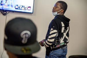 a man wearing a costume: Kyle Williams plays video basketball at New Options More Opportunities, a North Philadelphia-based youth mentoring organization.