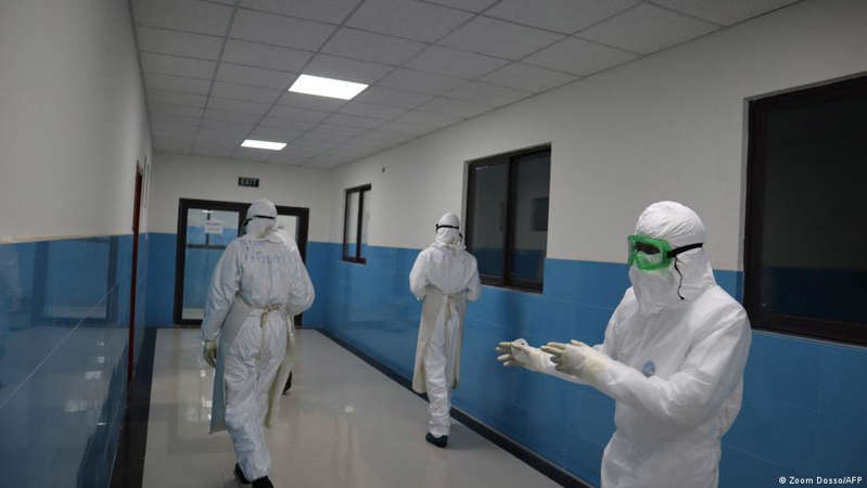 a man standing in a room: Africa is experiencing a spike in the number of infections and deaths from COVID-19