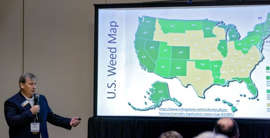 a man standing in front of a screen: David Chapman, property broker and developer, professor, state real estate commission member, and Edmond City Council member, talks about medical marijuana at a previous conference presented by the Central Oklahoma Association of Real Estate.