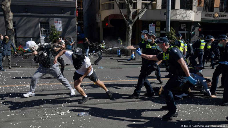 a group of people walking down the street: Thousands of protesters clashed with police in the Australian city of Melbourne