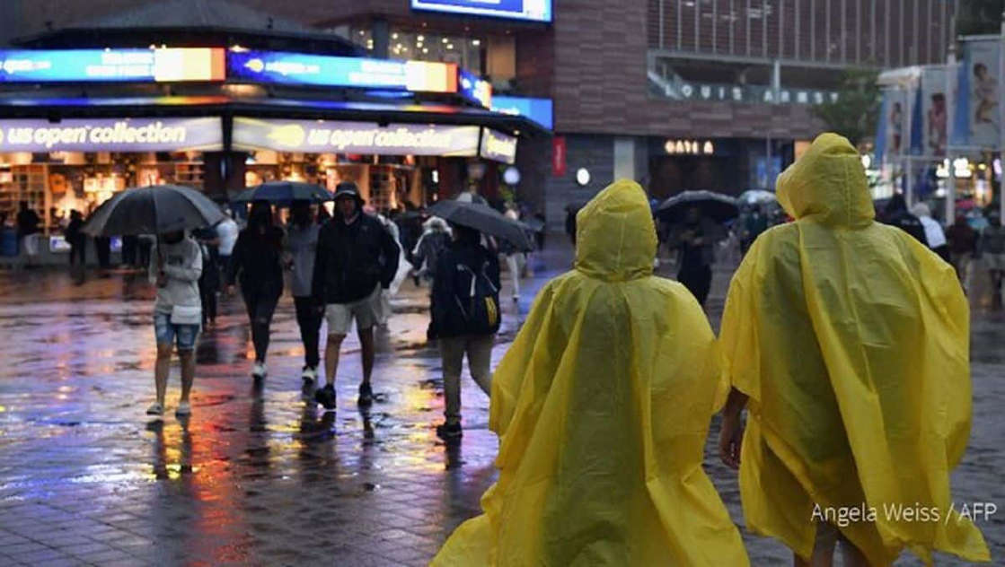 a group of people walking in the rain holding an umbrella: New Yorkers were inundated by flash flooding and heavy rains Thursday as Storm Ida wrought further havoc on the northeast US. (Photo: AFP)