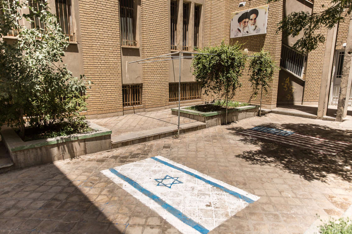 a stone building: An Israeli flag is painted on the ground outside a religious school in the Iranian city of Qom. The flag is near the entrance to the school so that it can be repeatedly trampled on as an insult to Israel, Iran's arch-enemy.