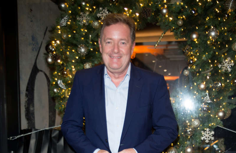 Piers Morgan wearing a suit and tie smiling at the camera